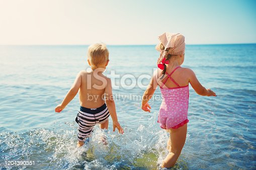 Boy and girl playing on the beach on summer holidays. Children in nature with beautiful sea, sand and blue sky. Happy kids on vacations at seaside running in the water