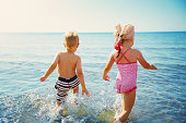 istock Boy and girl playing on the beach on summer holidays 1204390351