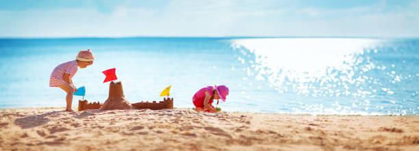 garçon et fille jouant sur la plage - chateau de sable photos et images de collection