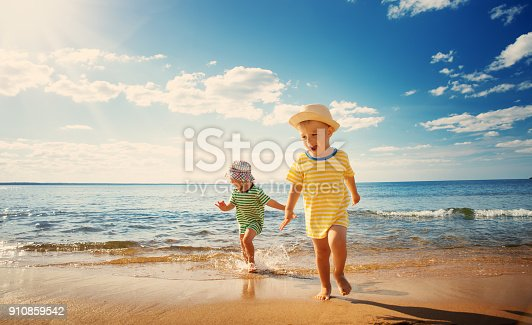 istock Boy and girl playing on the beach 910859542