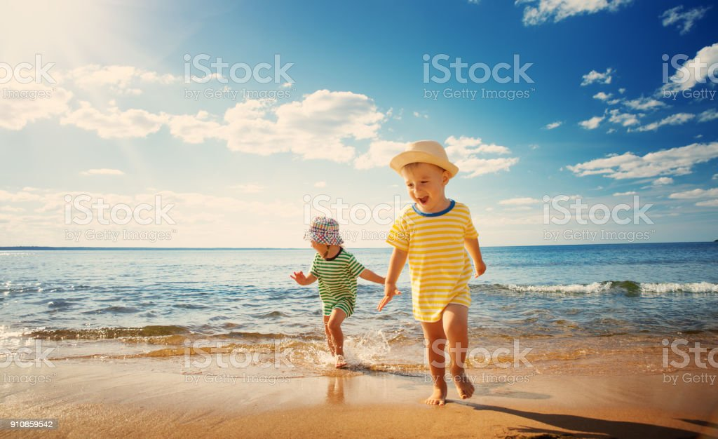 Boy and girl playing on the beach stock photo