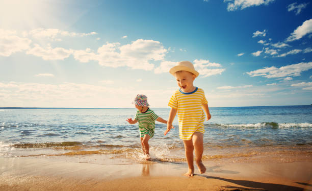 boy and girl playing on the beach - beach stock pictures, royalty-free photos & images
