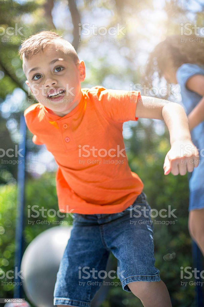 Boy and girl playing on trampoline stock photo