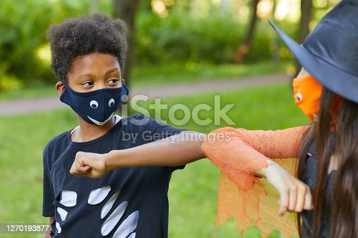 African boy in costume playing with his friend in the park outdoors