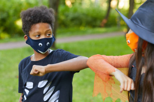 garçon et fille jouant à l'extérieur - masque enfant photos et images de collection