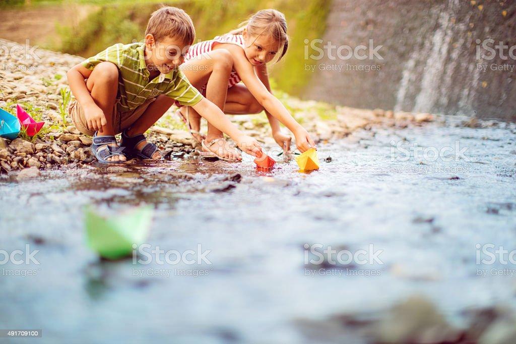 Menina e menino tocando papel barcos no rio - foto de acervo