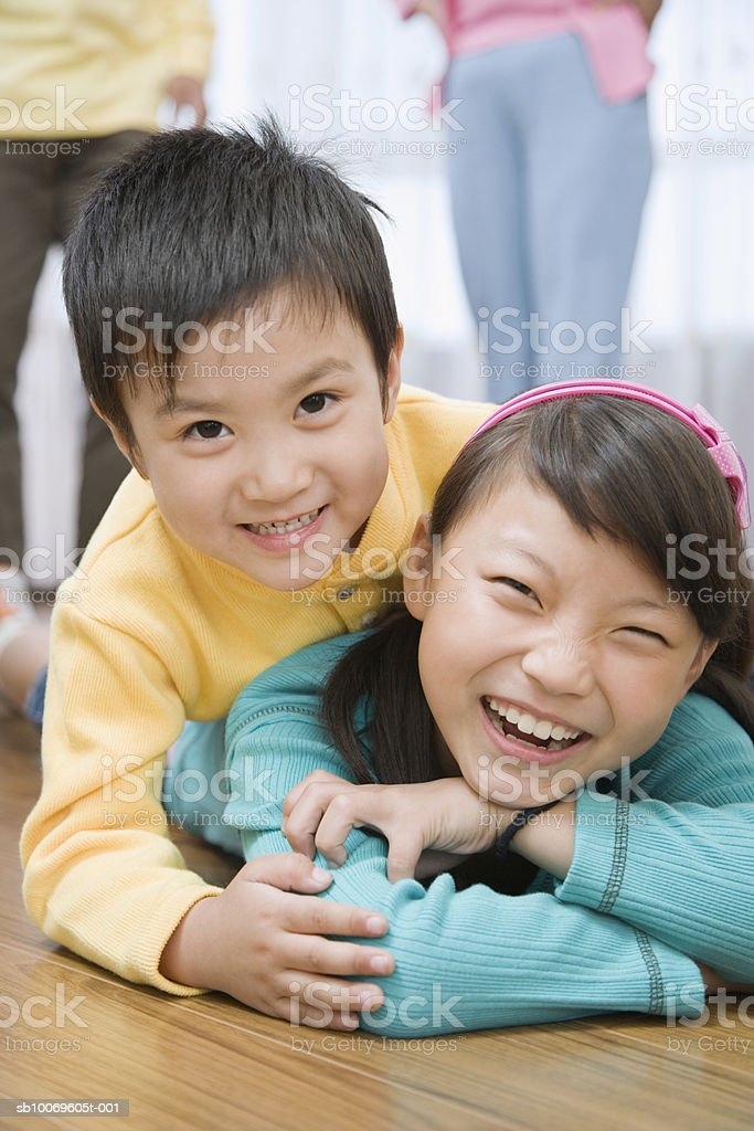 Boy (4-5) and girl (8-9) playing, smiling foto de stock royalty-free