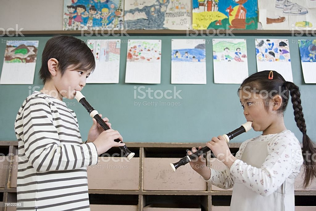 A boy and girl playing the recorder 免版稅 stock photo