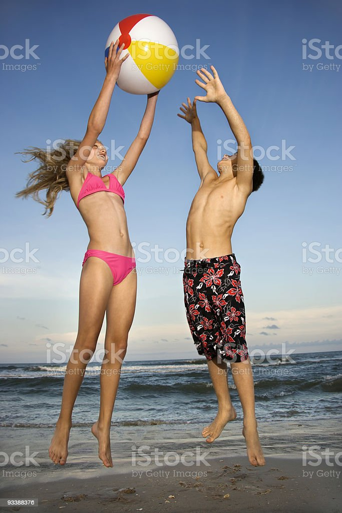 Boy and girl playing with ball on beach. stock photo