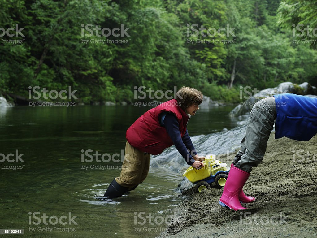 Boy and girl playing with trucks on river bank. royalty free stockfoto