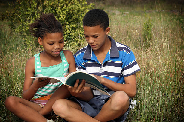 Boy and girl reading African boy and girl reading outdoor. illiteracy stock pictures, royalty-free photos & images