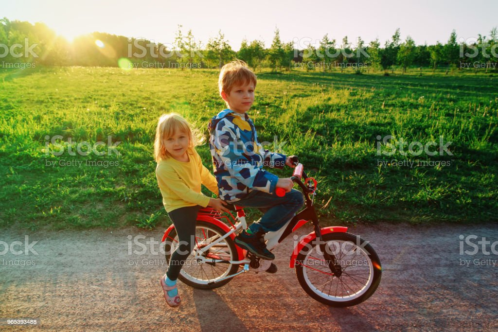 boy and girl riding bike in sunset nature royalty-free stock photo