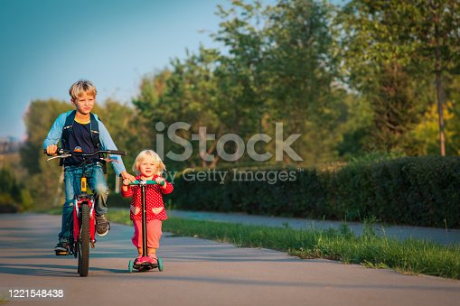 665192886 istock photo boy and girl riding scooter and bike outside, kids exercise outdoors 1221548438