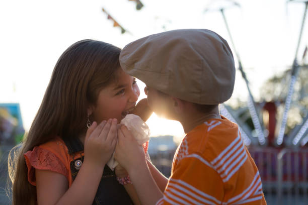 Boy and Girl Sharing Snack at a Carnival stock photo