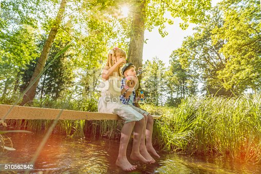 618034312 istock photo Boy and girl sitting above small stream blowing soap bubbles 510562842