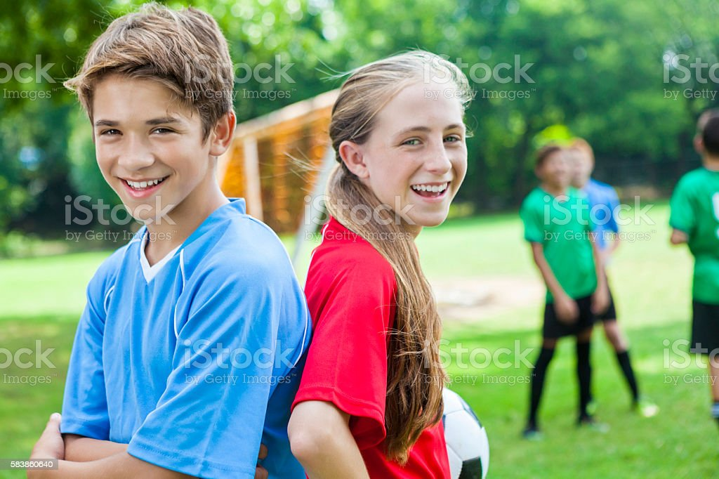 Boy and girl soccer players back to back on field stock photo