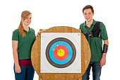 Young boy and girl standing besides the bull's eye of an archery target