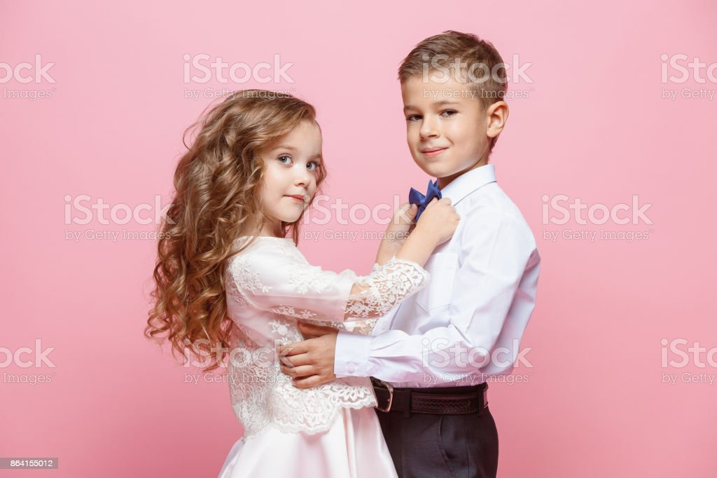 Boy and girl standing in studio on pink background royalty-free stock photo