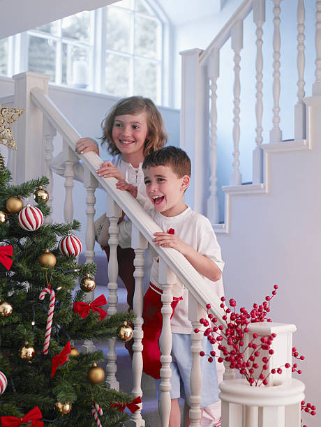 boy and girl standing on stairs above christmas tree - christmas tree stockfoto's en -beelden