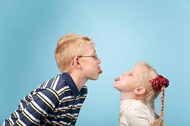 A boy and girl sticking their tongues out at each other stock photo