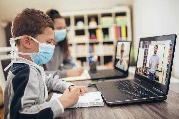 Boy and girl studies at home, wear protective masks, and doing school homework. Distance learning online education.online education. stock photo