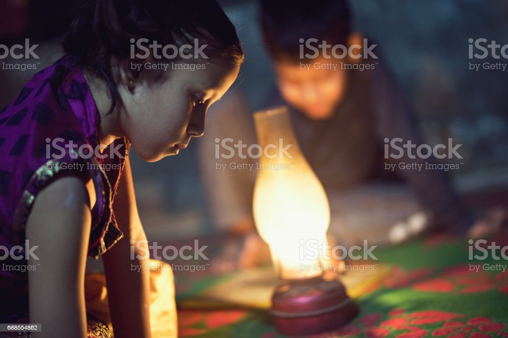 Boy and girl studying in oil lamp stock photo