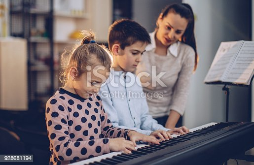 Boy and girl teaching to play synthesizer in music school