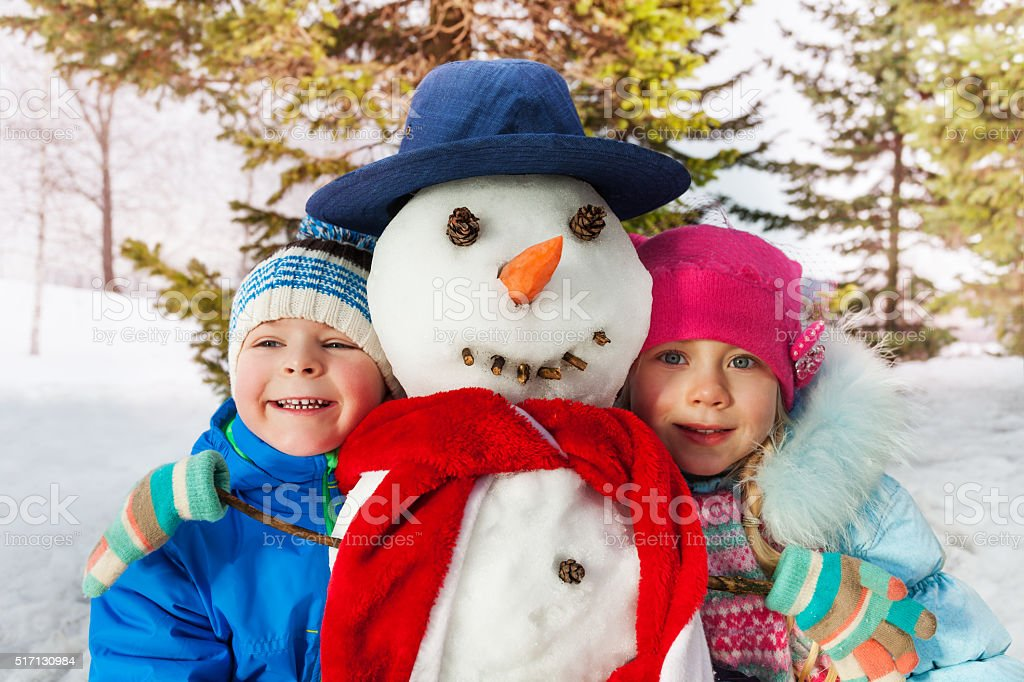 Boy and girl together with dressed snowman stock photo