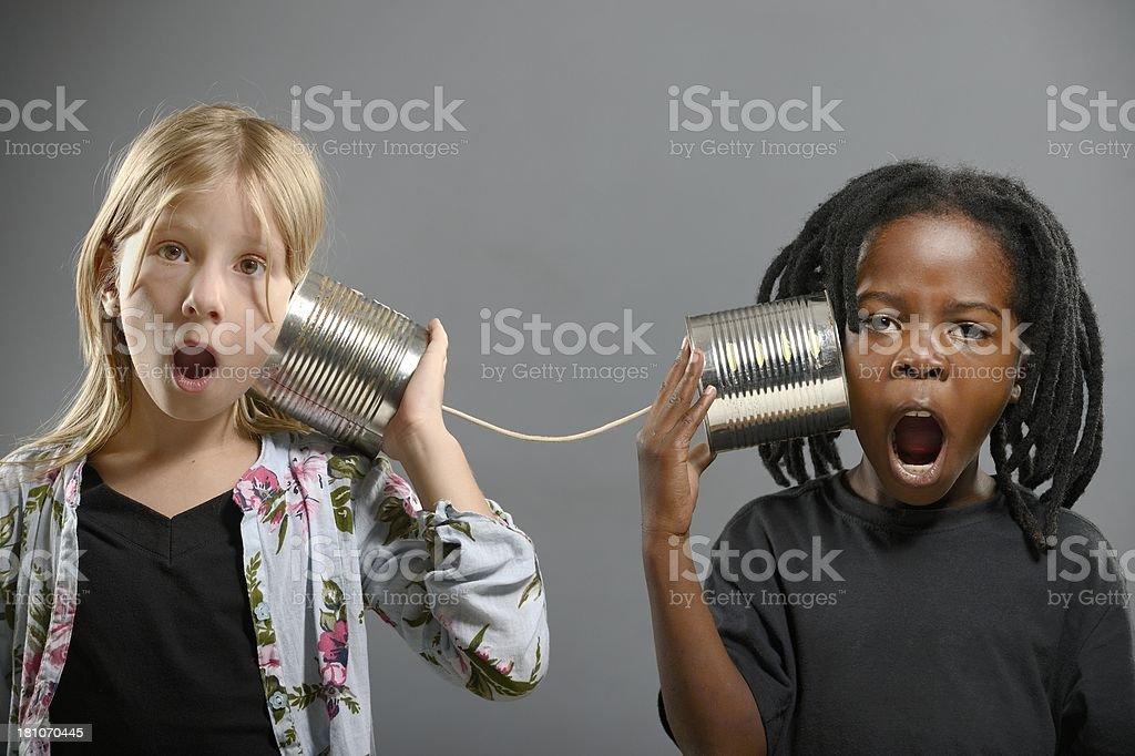 Boy and girl using tin telephone stock photo