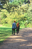 istock Boy and girl walking along woodland pathway / footpath, holding-hands, red-hair 525738313