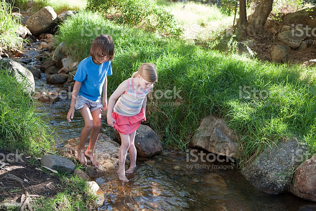 Boy and girl walking in river royalty-free stock photo