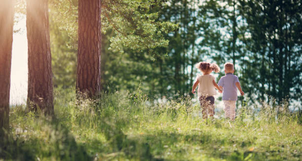 Boy and girl walking in the forest in summer stock photo