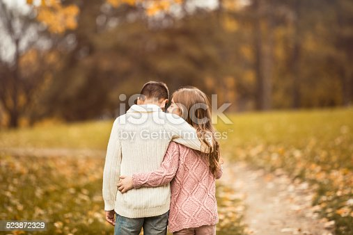 585604690istockphoto Boy And Girl Walking Together In Autumn Park 523872329