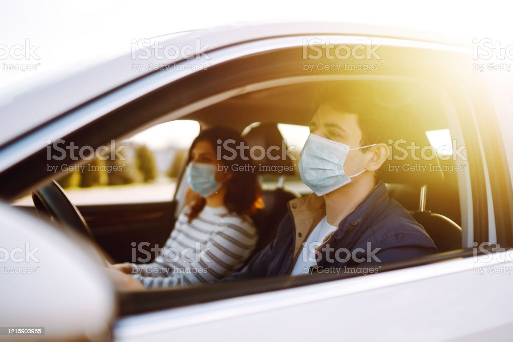 Chico y niña usan máscara médica estéril protectora en el coche. - Foto de stock de Adulto libre de derechos