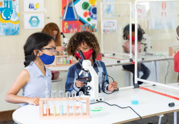 Boy and girl wearing face mask using microscope in laboratory stock photo