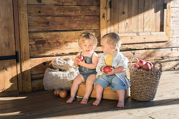 Boy and Girl with apples near wooden house stock photo