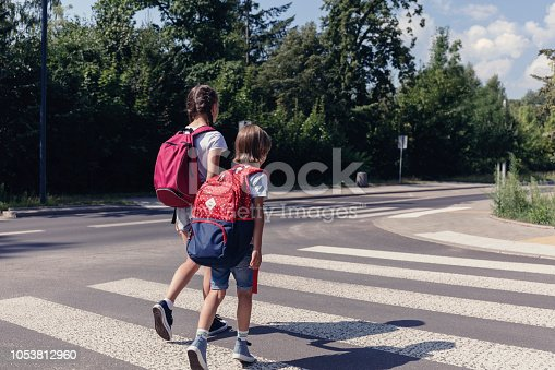 Boy and girl with backpacks walking on pedestrian crossing to the school