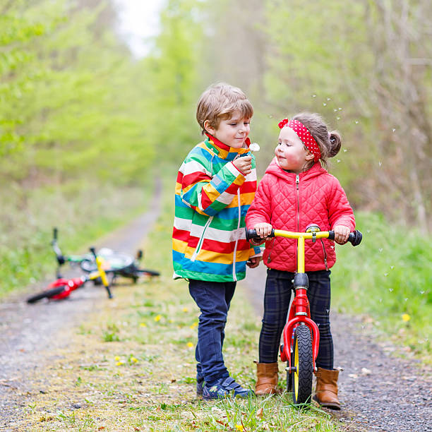 boy and girl with bicycles and blowing dandelion - little girls little boys kissing love stock photos and pictures