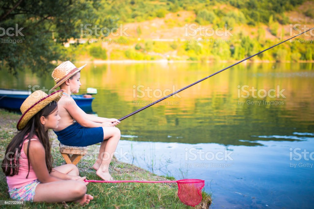 Boy and girl with fishing rods stock photo