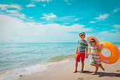 boy and girl with floatie go to beach, family on summer vacation