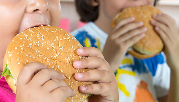 boy and girl with hamburgers - fast food restaurant stock pictures, royalty-free photos & images