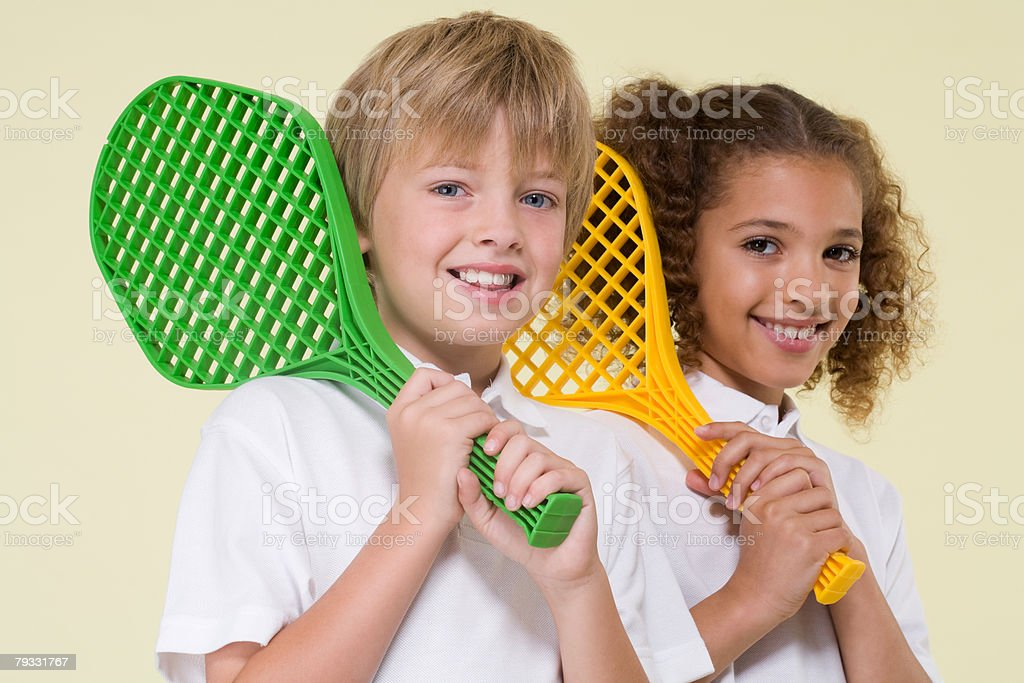 Boy and girl with tennis rackets royalty-free stock photo
