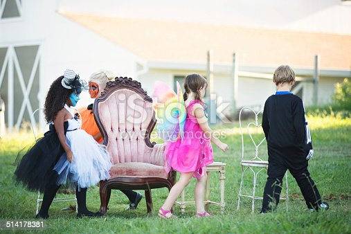 Boy and girls in costume playing musical chairs at a Halloween party.