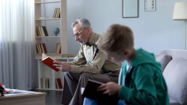 junge und großvater lesebücher, begriff der bildung in jedem alter - gedichte zum ruhestand stock-fotos und bilder
