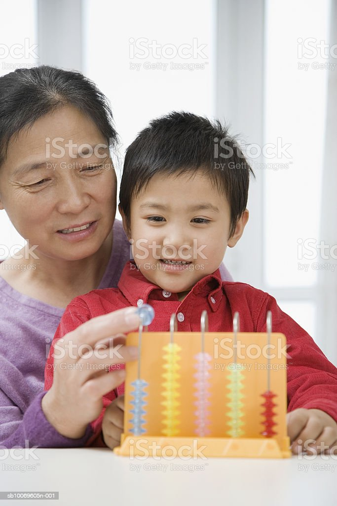 Boy (4-5) and grandmother playing with abacus royalty free stockfoto