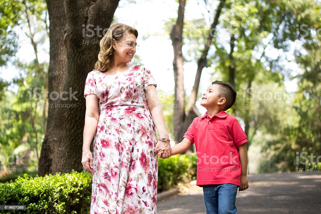 A preschool latin boy and his grandmother walking hand in hand at the...
