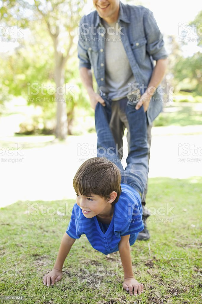 Boy and his dad play in the park stock photo