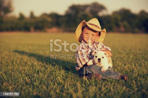 A young American boy with his dog on the farm.