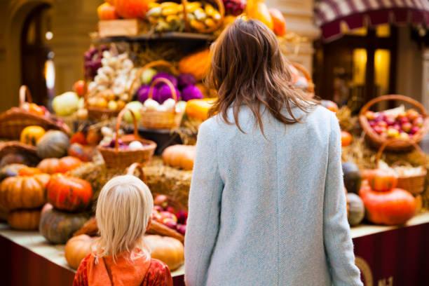 junge und seine mutter auf dem bauernmarkt - kürbis kaufen stock-fotos und bilder
