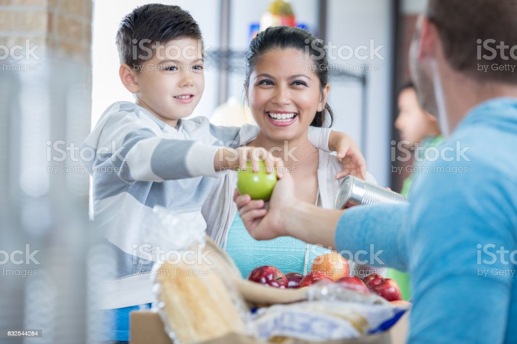 Boy and his mom donate apples to community food drive stock photo